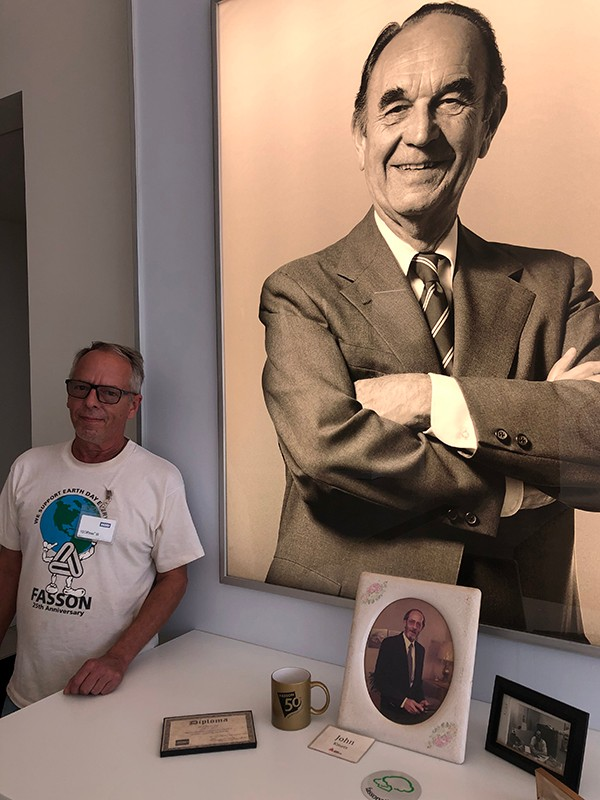 "Tim Kmetz poses in front of a photo of his father, Avery Dennison employee John Kmetz (table) and Avery Dennison Founder, Stanton ""Stan"" Avery (wall)."